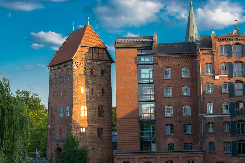 View of a hotel in the German city of Lüneburg. Beautiful cityscape with reflections of houses on water and sky with clouds. Architecture Built Structure Building Exterior Building Sky Cloud - Sky The Past History City Window Tower Low Angle View No People Nature Travel Destinations Tourism Day Outdoors Place Of Worship Spire