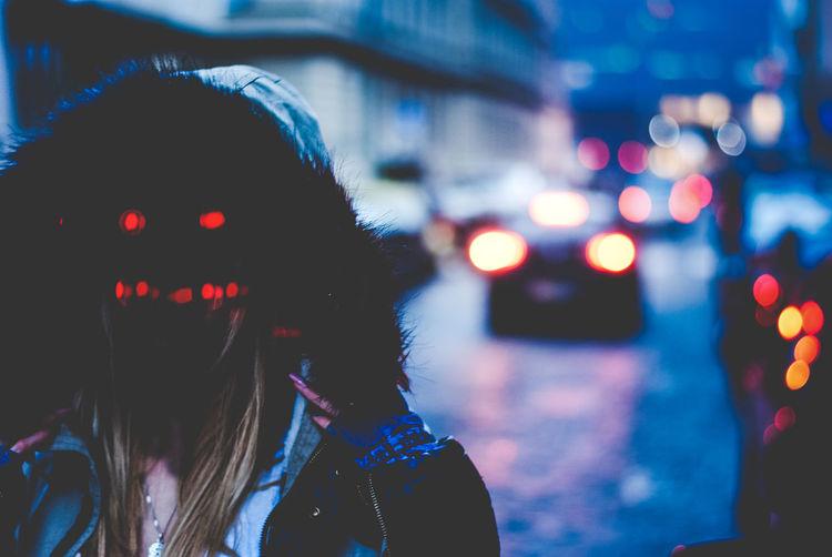 Woman wearing spooky illuminated mask on street at dusk