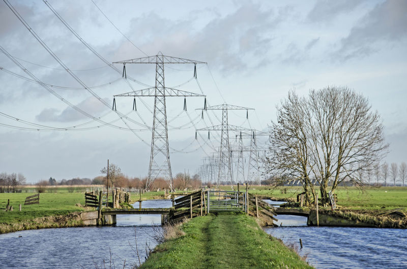 Electricity pylon by canal against sky