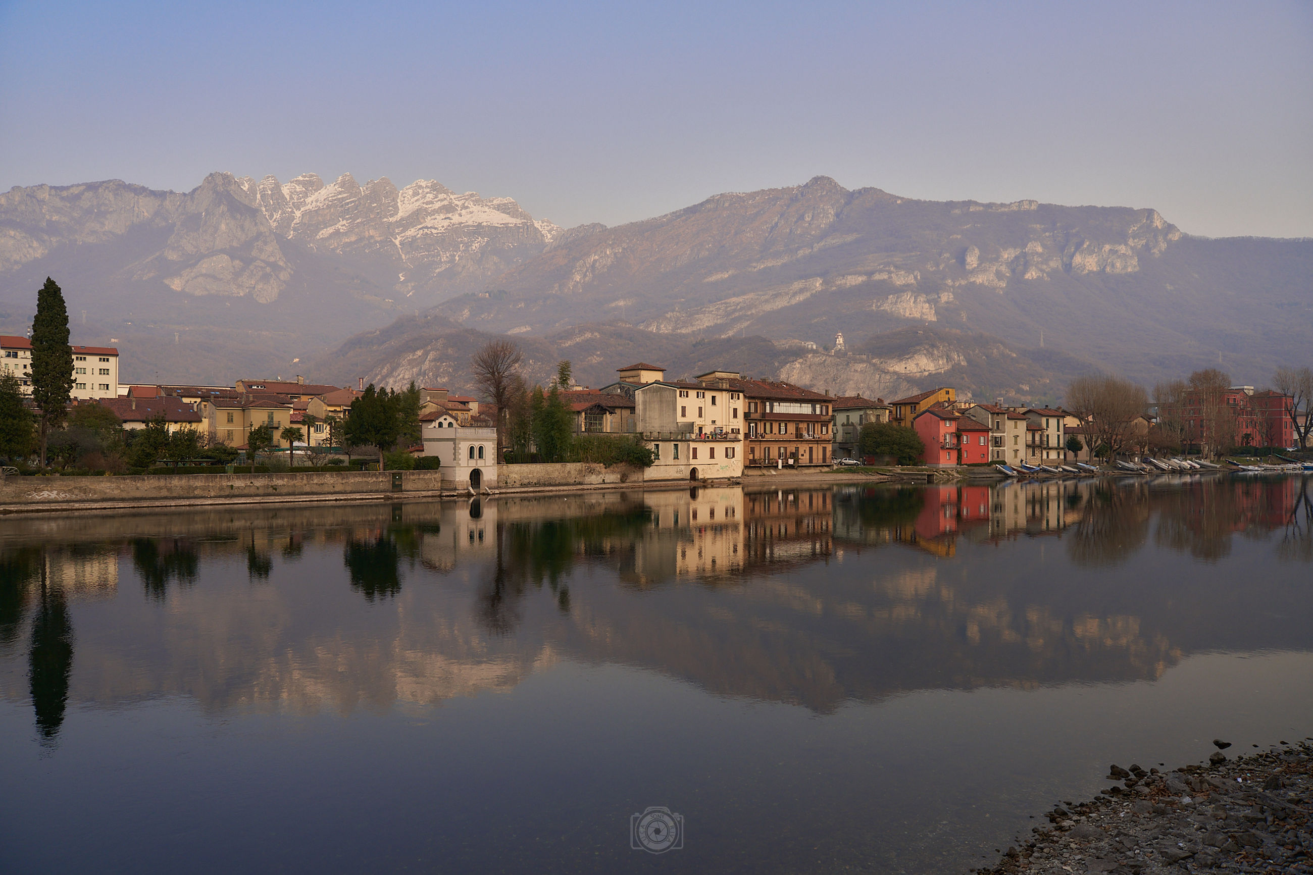 water, reflection, mountain, architecture, morning, building, sky, building exterior, built structure, lake, nature, mountain range, landscape, city, scenics - nature, travel destinations, house, environment, beauty in nature, dusk, travel, no people, religion, land, outdoors, tranquility, residential district, tourism, clear sky, history, tree, town, twilight, the past, blue