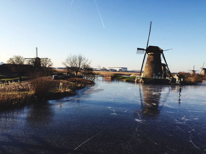 Water Windmill Alternative Energy Fuel And Power Generation Renewable Energy Environmental Conservation Wind Power Wind Turbine Nature Built Structure Waterfront Outdoors No People Clear Sky River Sky Architecture Day Factory Watermill Ice Cold Cold Temperature Ice Skating