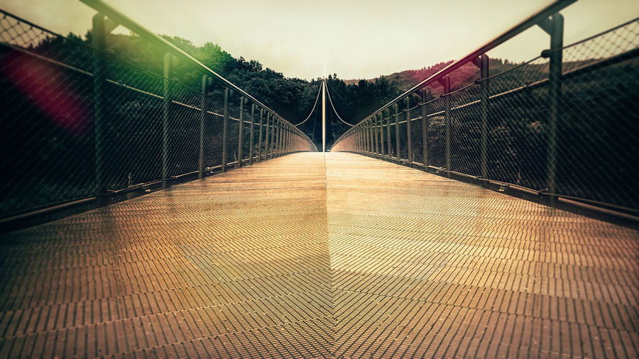 Narrow footbridge over bridge against sky