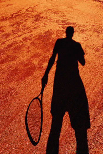 Shadow of man with umbrella standing on floor