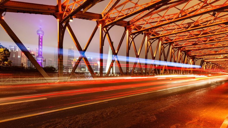 Low angle view of light trails on suspension bridge at night