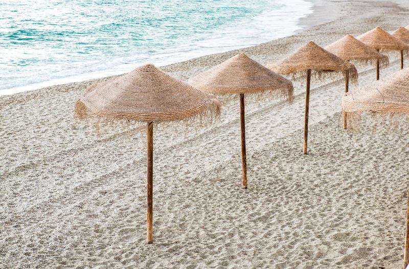 Straw parasols on empty beach. Nerja, Spain Andalucía Beach Coast Coastline Costa Del Sol Empty In A Row Landscape Malaga Mediterranean Sea Nature Nerja No People Nobody Outdoors Resort Sand Sandy Beach Seashore Seaside SPAIN Straw Umbrellas Sun Umbrellas Vacations