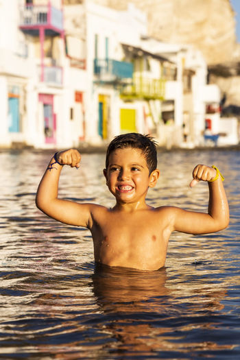 Shirtless boy flexing muscles in sea