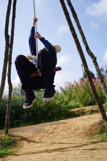 Low angle view of man enjoying on swing against sky