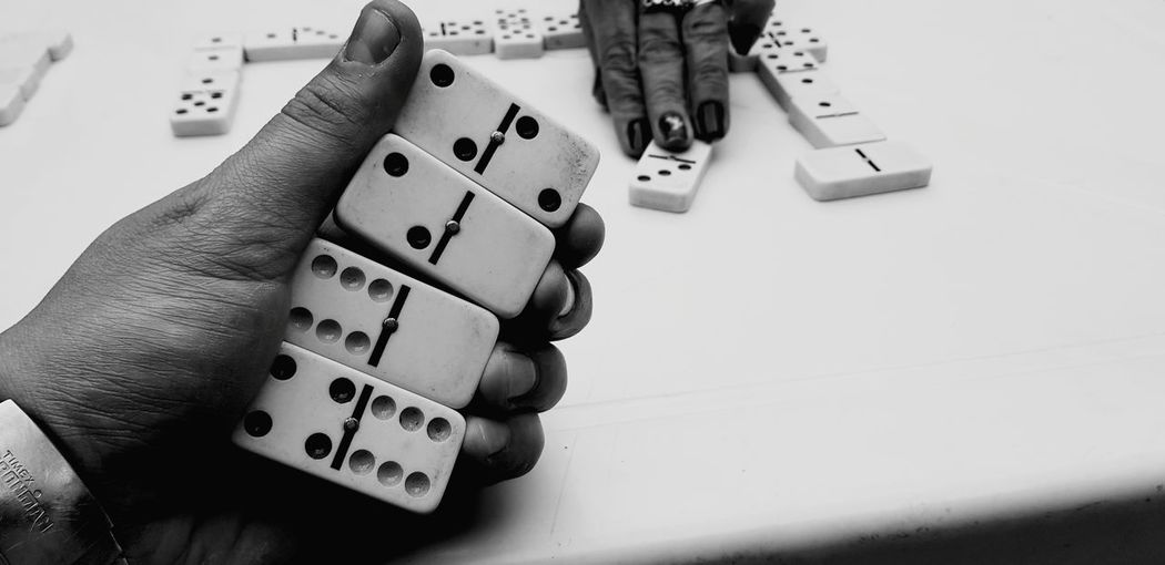 Cropped hands of friends playing dominoes at table