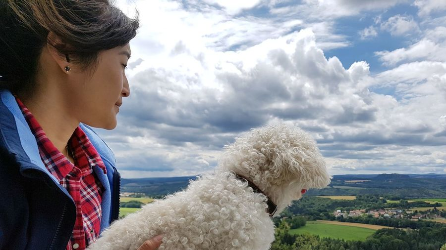 Young woman with dog standing on mountain against cloudy sky