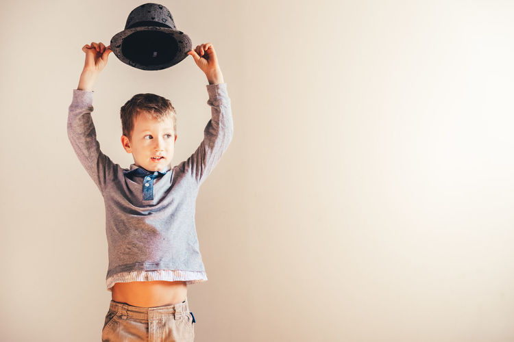 Boy holding hat against white wall