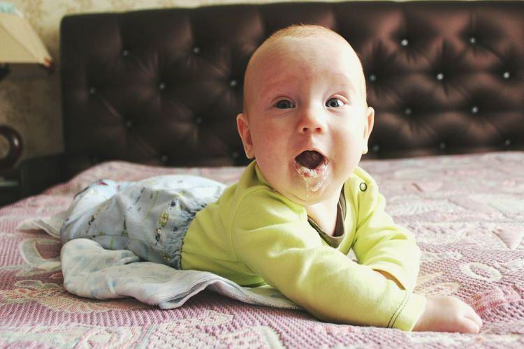 Close-up portrait of cute baby boy drooling on bed at home