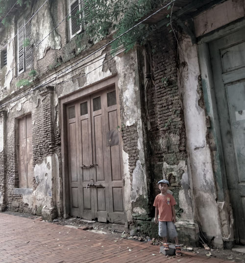 Rear view of a man standing on window of old building