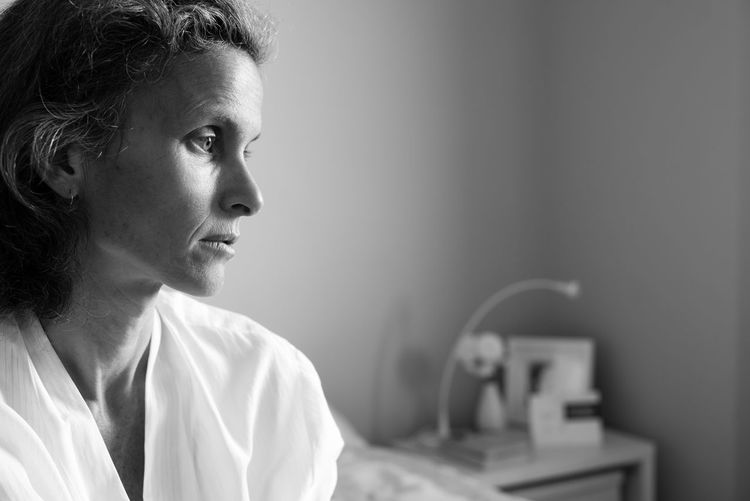 Profile view of sad middle aged woman in bedroom (black and white) Adults Only Bedroom Close-up Depressed Indoors  Mature Adult Morning One Person People Real People Sad Women
