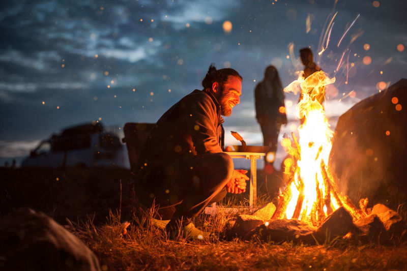 Side view of man crouching by campfire at night