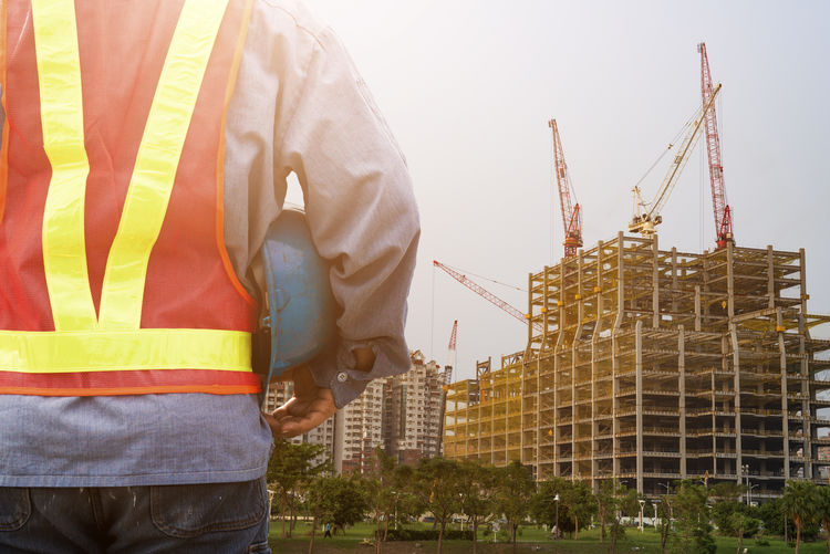 Midsection Of Engineer Standing At Construction Site Against Sky During Sunset