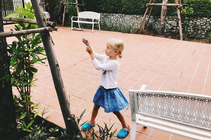 Blond Hair Casual Clothing Child Childhood Day Full Length Girls Hair Hairstyle Holding Innocence Leisure Activity Lifestyles One Person Outdoors Plant Playing Real People Standing Women