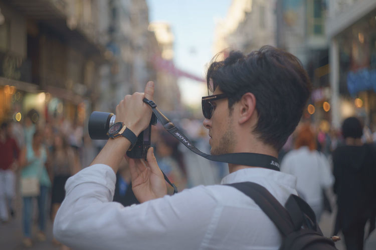 Side view of young man photographing through digital camera on street