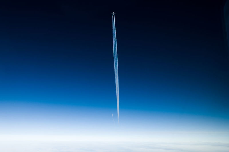Blue Vapor Trail Sky Flying Cloud - Sky No People Nature Air Vehicle Motion Copy Space Transportation Speed Airplane Beauty In Nature Day Mid-air Smoke - Physical Structure White Color Outdoors Blue Background