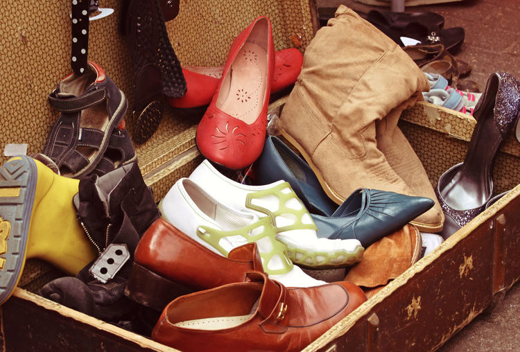 High angle view of various shoes in suitcase for sale
