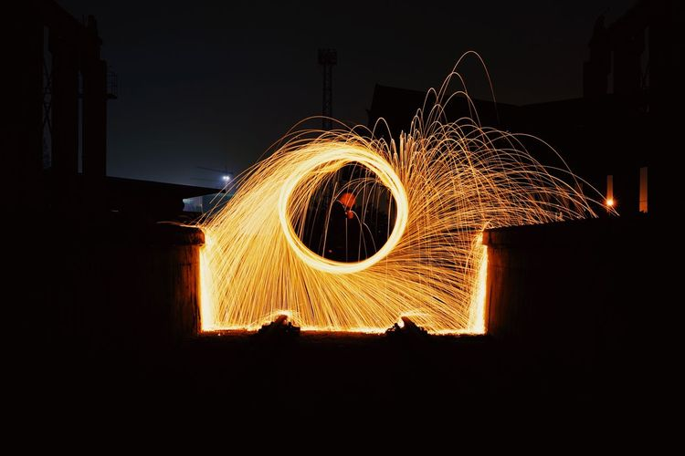 Man spinning wire wool outdoors at night