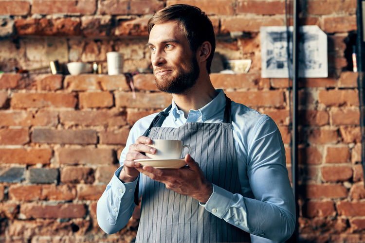 Portrait of young man with coffee cup against wall