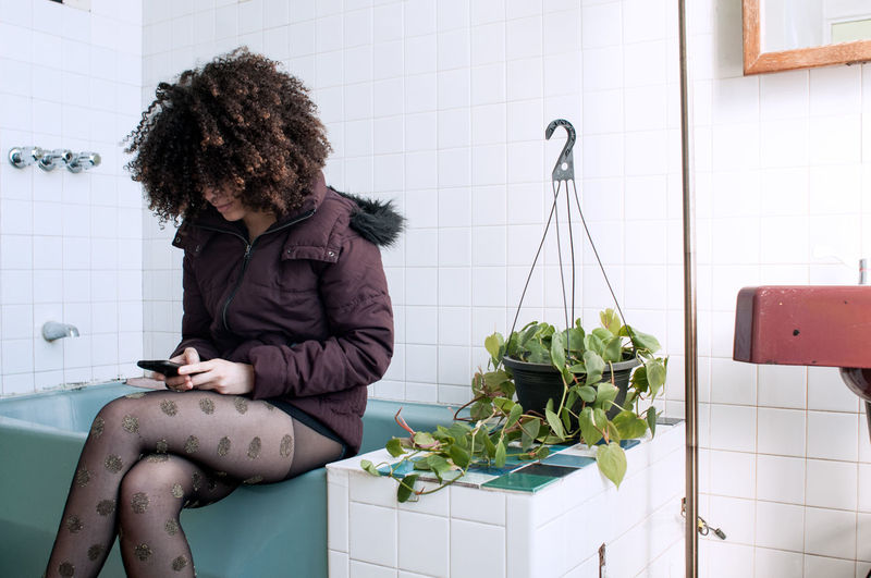 Young woman using mobile phone while sitting on bathtub