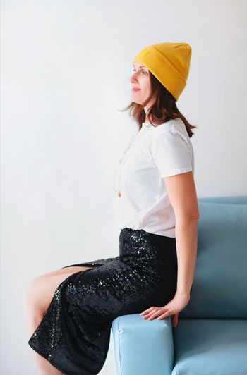Midsection of woman sitting against wall