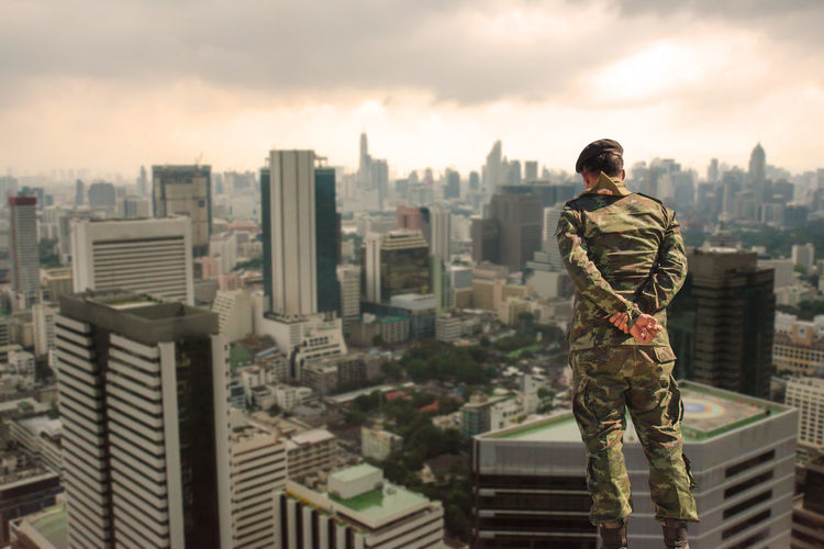 Rear View Of Army Soldier Looking At Cityscape