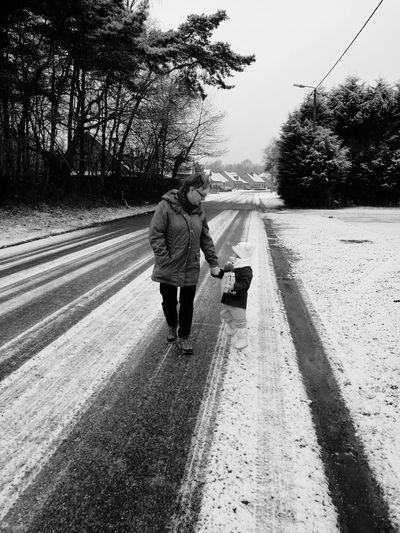 Mother and son walking on snow covered road