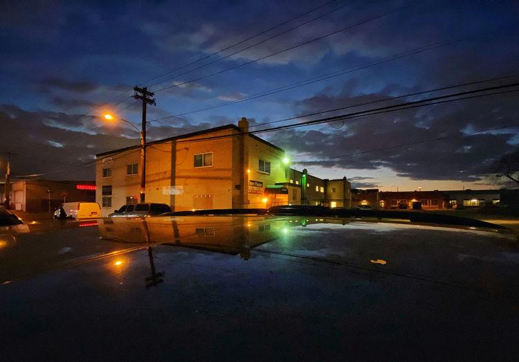 Illuminated street by buildings against sky at dusk