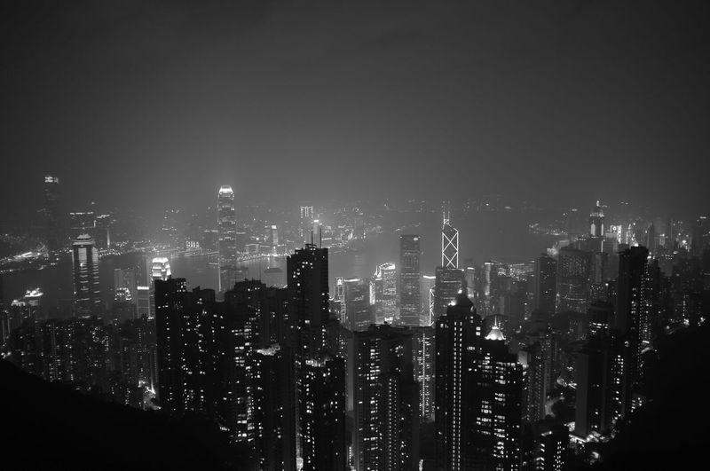 Illuminated cityscape at victoria harbour against sky