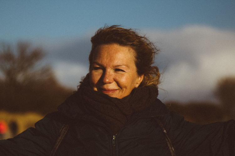 Portrait of smiling woman against sky during winter