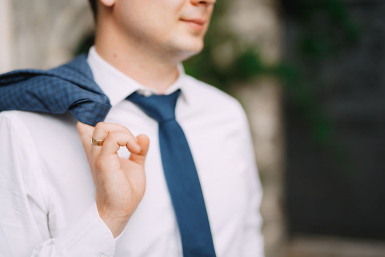 Midsection of man standing against blurred background