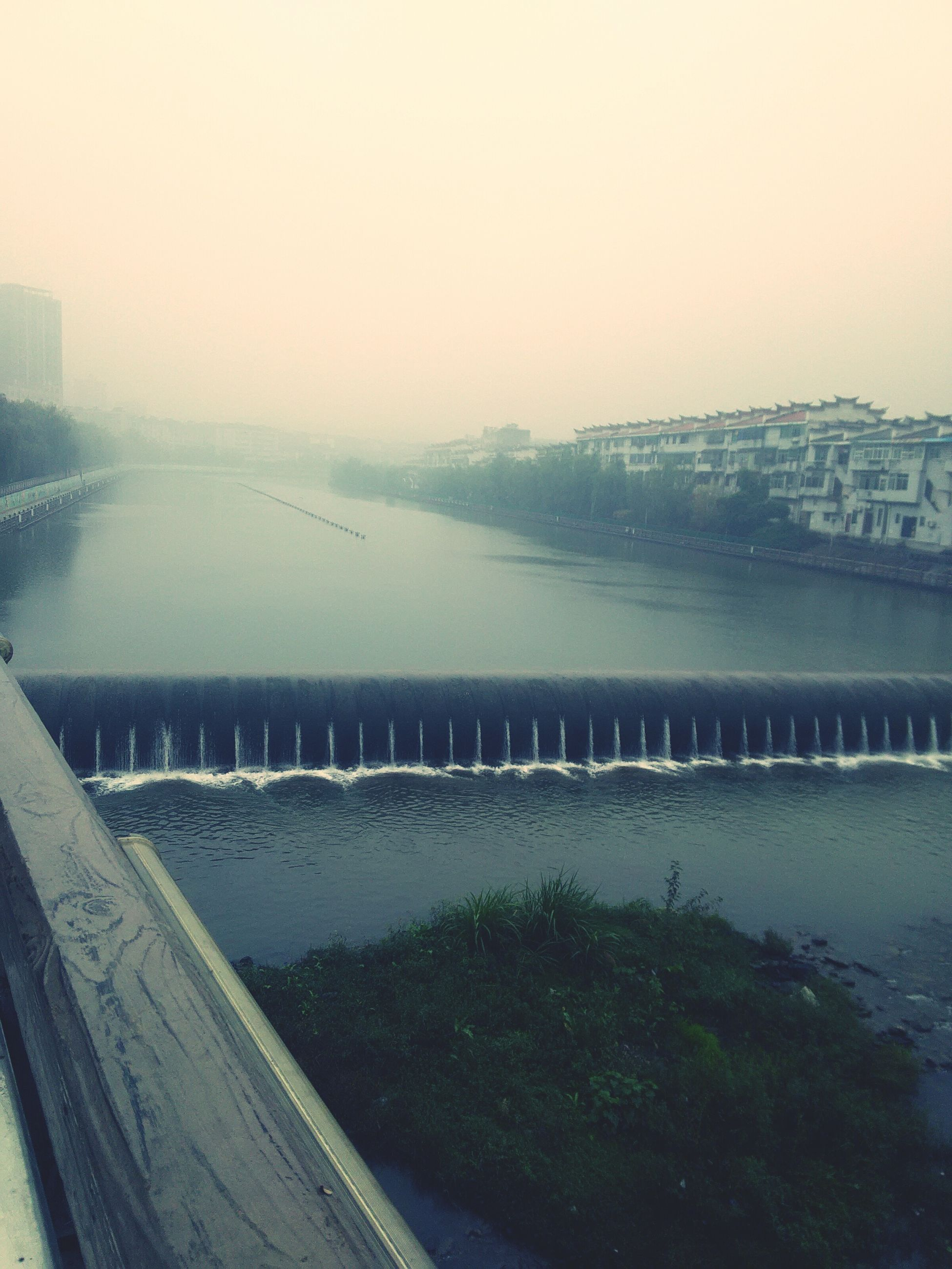 water, built structure, river, architecture, clear sky, building exterior, city, foggy, weather, nature, copy space, sky, season, railing, cityscape, transportation, bridge - man made structure, day, outdoors
