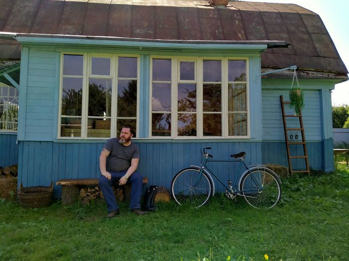 Man sitting on bicycle outside house
