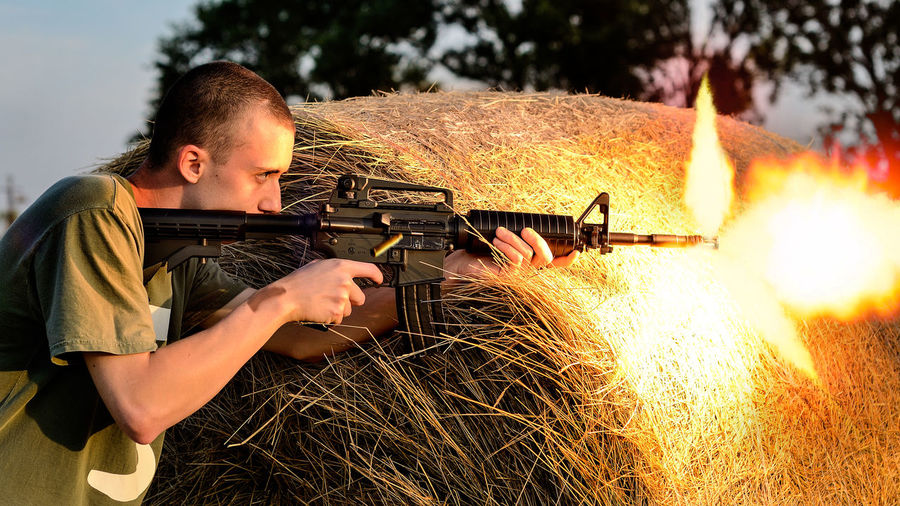 Side View Of Young Man Shooting With Rifle Against Hay Bale