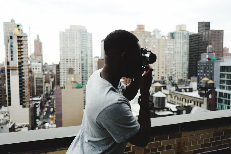 Digital composite image of woman photographing cityscape