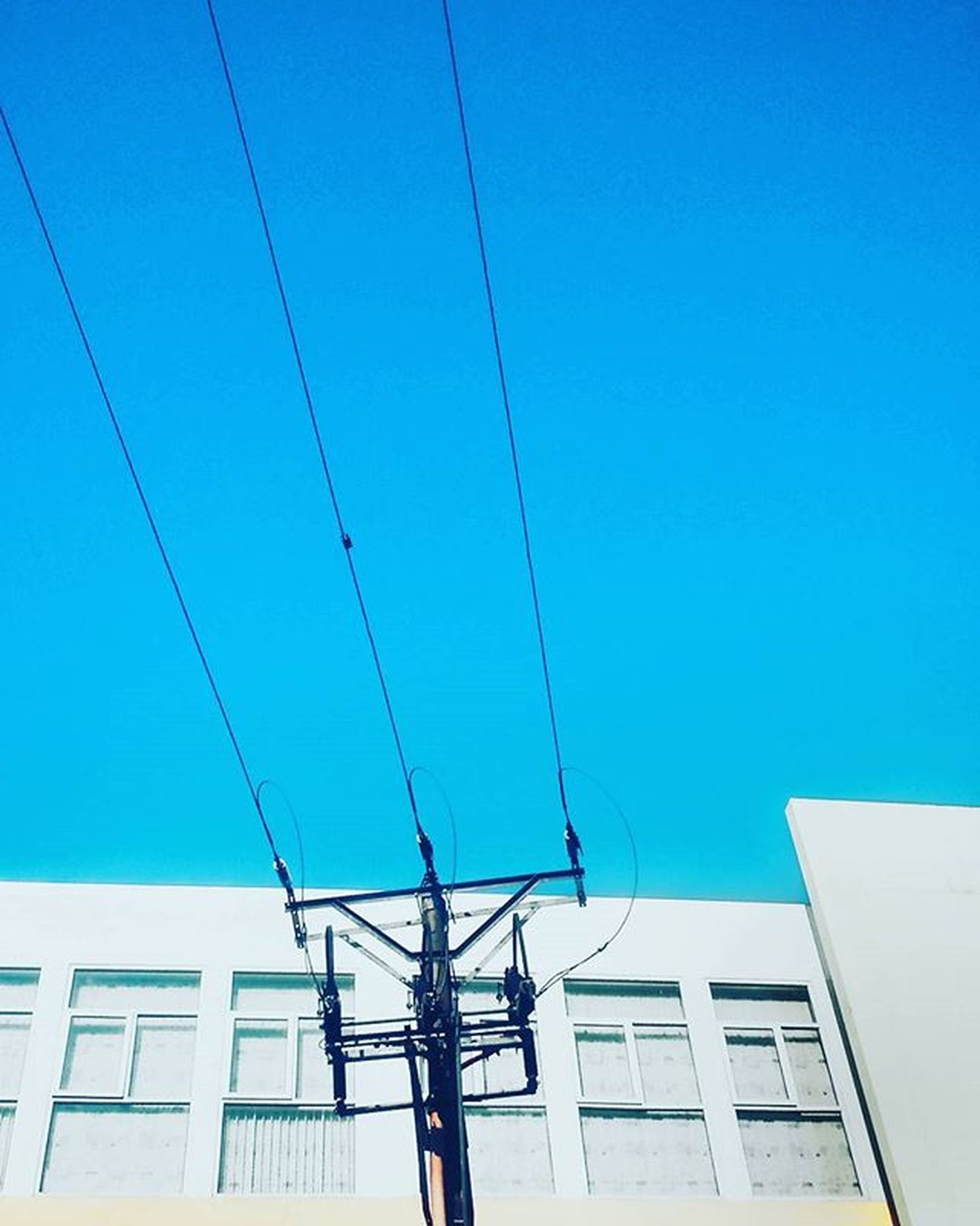 clear sky, blue, low angle view, built structure, architecture, building exterior, power line, cable, electricity, copy space, connection, power supply, day, technology, electricity pylon, building, sunlight, outdoors, fuel and power generation, no people