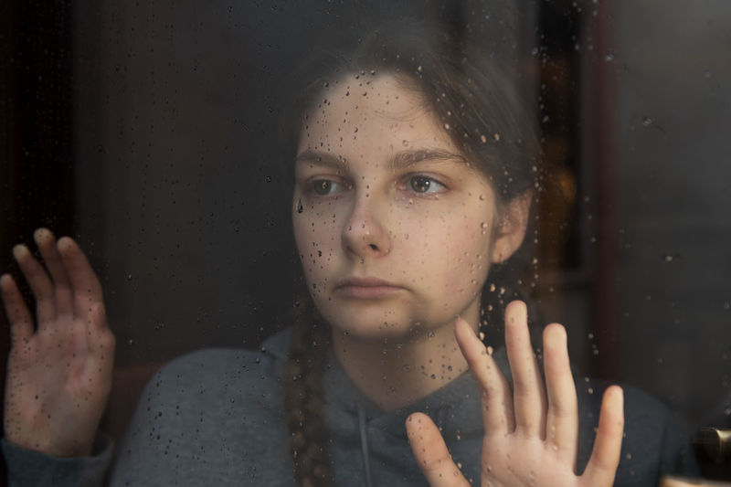 Young girl is looking with hope the window on which raindrops, autumn mood, loneliness