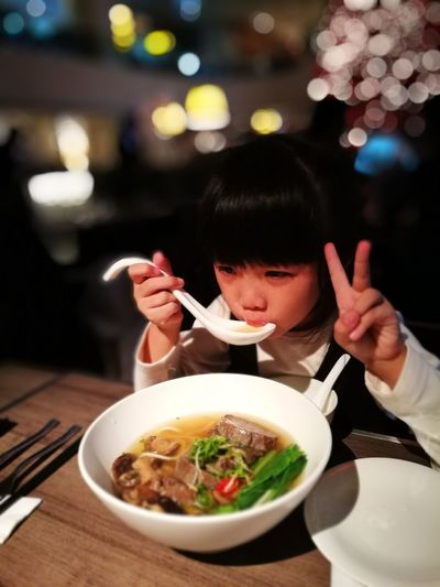 Girl Showing Peace Sign While Having Soup At Table In Restaurant