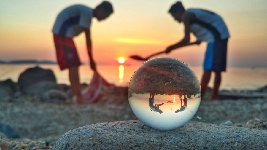 Close-up of ball on beach against sky during sunset