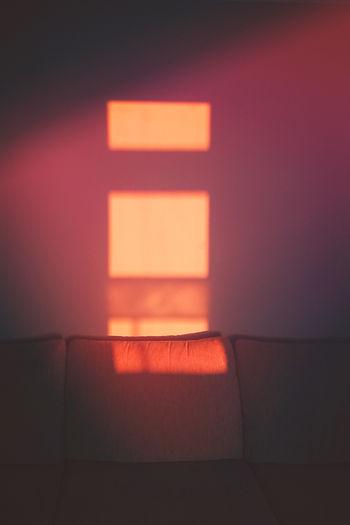 Illuminated lamp on wall at night