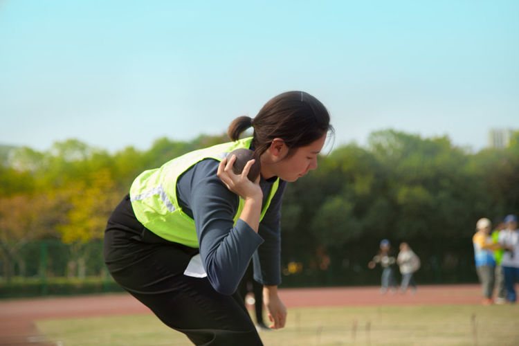 Side view of woman playing shot put at park against sky