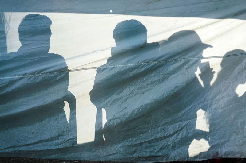 Shadows of friends on tarpaulin outdoors