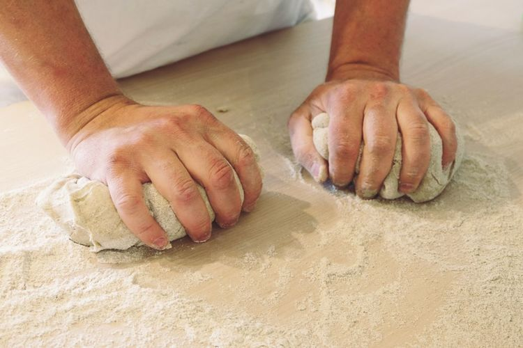 Cropped Image Of Person Kneading Dough On Table