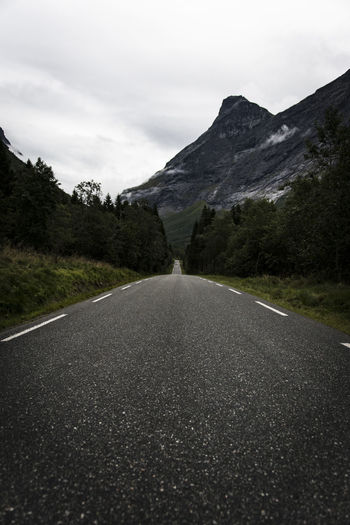 Surface level of road amidst mountains against sky
