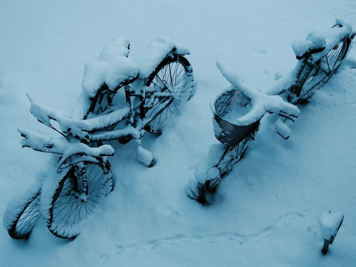 High Angle View Of Bicycles Parked On Snow Covered Field