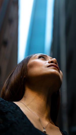Low Angle View Of Thoughtful Woman Standing In City
