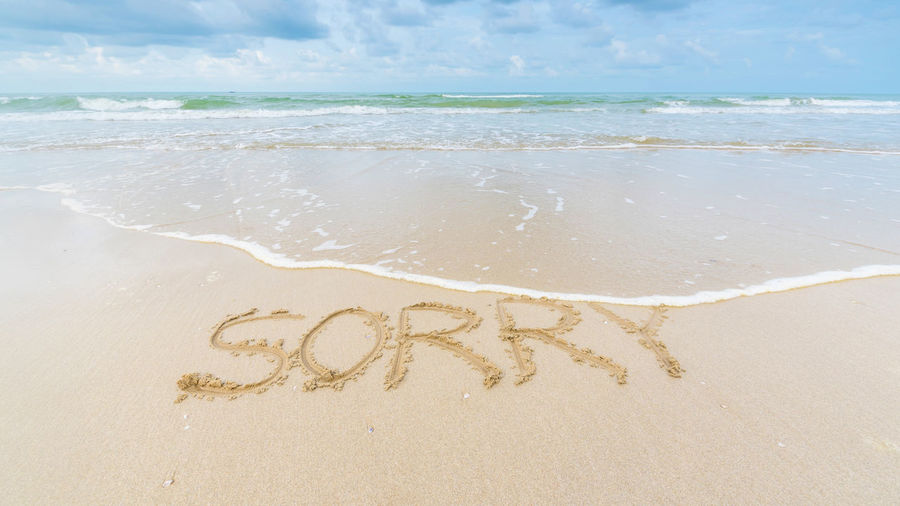 High angle view of sorry text on sand at beach against sky