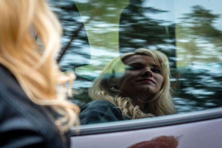 Woman reflecting on car window